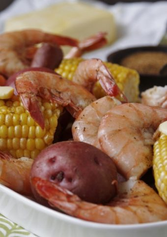shrimp, potatoes, sausage, and corn on white platter.