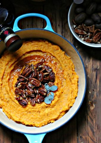 Boozy Smashed Sweet Potatoes in blue pot with bowl of pecans to side and bottle of bourbon