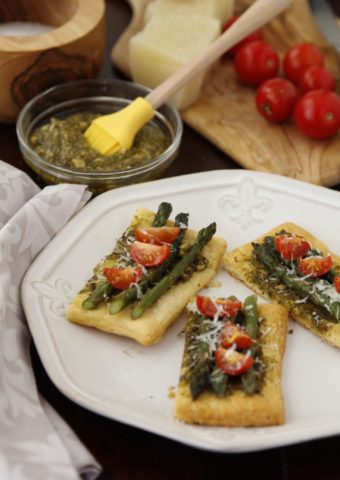 puff pastry appetizer with asparagus and tomatoes on white plate.
