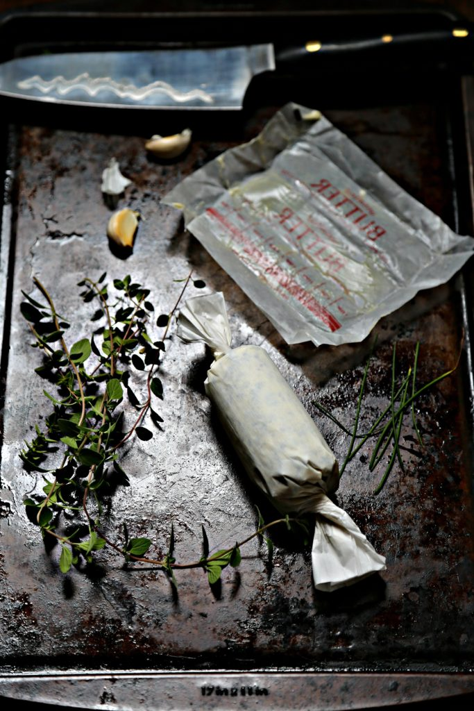 compound butter in parchment, fresh herbs, butter wrapper and garlic cloves on baking sheet.
