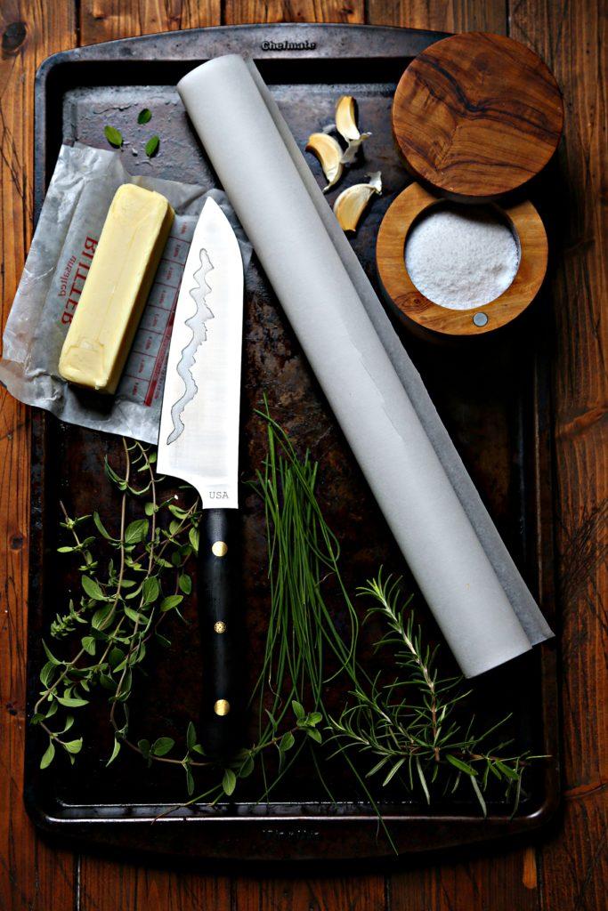 butter, knife, parchment paper, salt cellar, fresh herbs and garlic cloves on baking sheet.