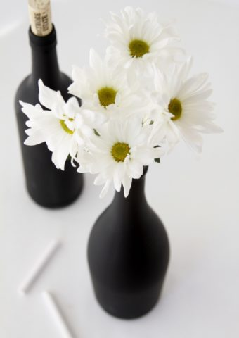 diy chalkboard painted wine bottles, one with daisies and chalk to side