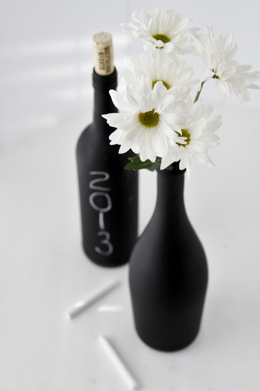 wine bottles painted with chalkboard paint, one with year drawn on and other filled with daisies