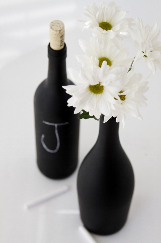 wine bottles painted with chalkboard paint, one filled with daises