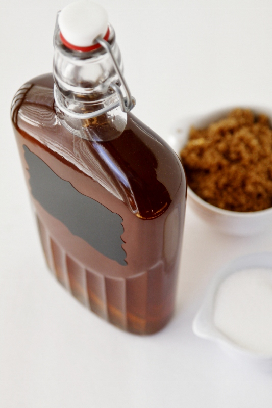 Bottle of homemade amaretto with bowl of brown sugar