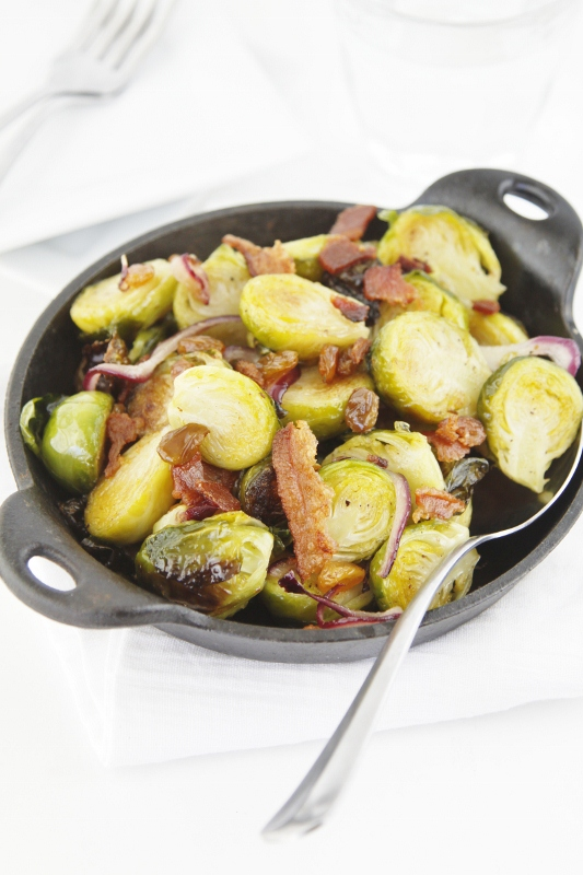 Roasted brussels sprouts with bacon in small cast iron pan with serving spoon.