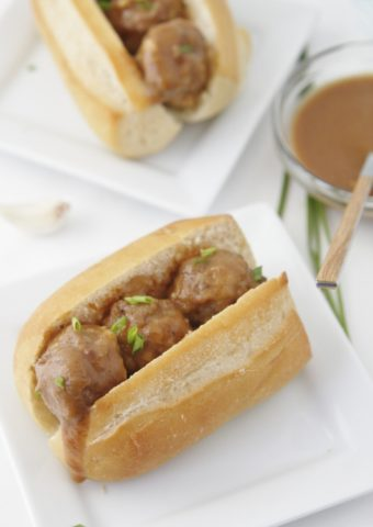 Mini meatball subs on white plates. Glass bowl of sauce in background.