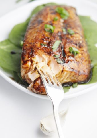 glazed salmon on bed on spinach on white plate with fork.