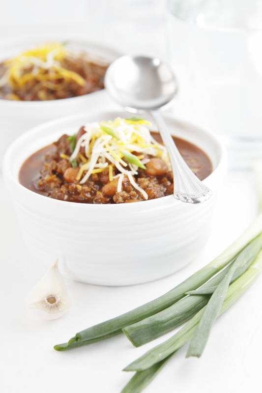 2 small bowls of chili topped with shredded cheese.
