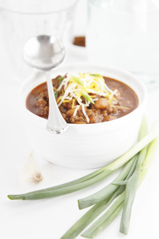small bowl of chili with spoon. Scallions in foreground.
