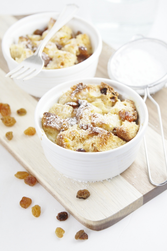 2 small white ramekins with bread pudding on board. Raisins scattered around. Small sifter to side.