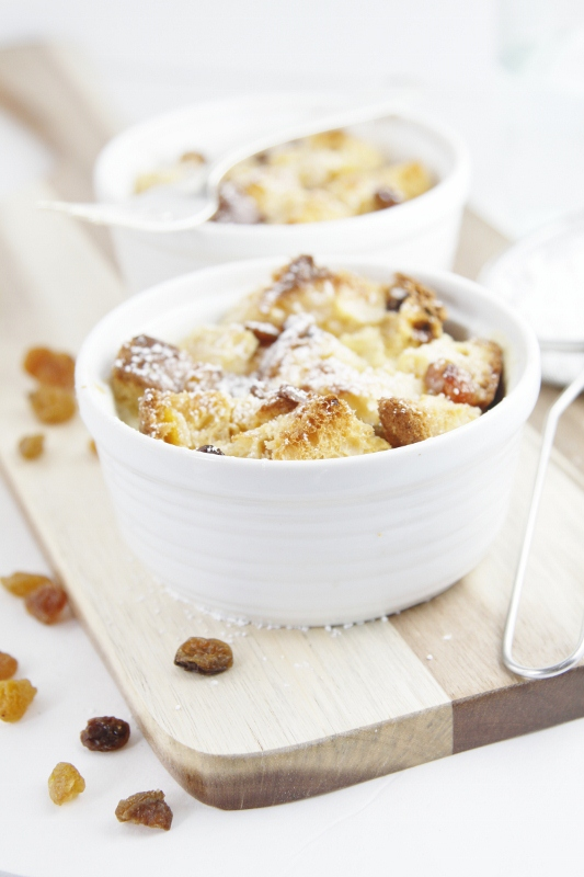 2 small white ramekins with bread pudding on board. Raisins scattered around. Sifter to side.