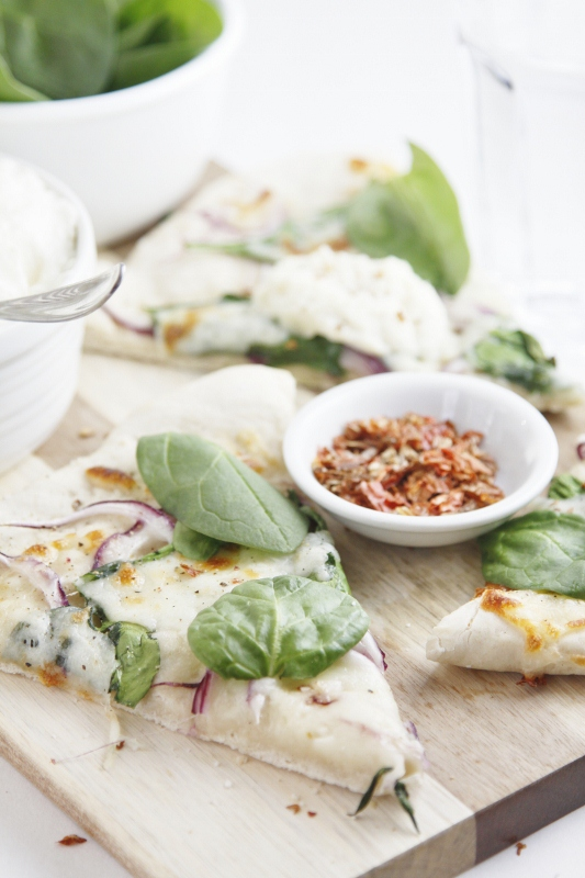 slices of spinach ricotta pizza on cutting board. Small white bowls of spinach, ricotta and red pepper flakes surrounding.