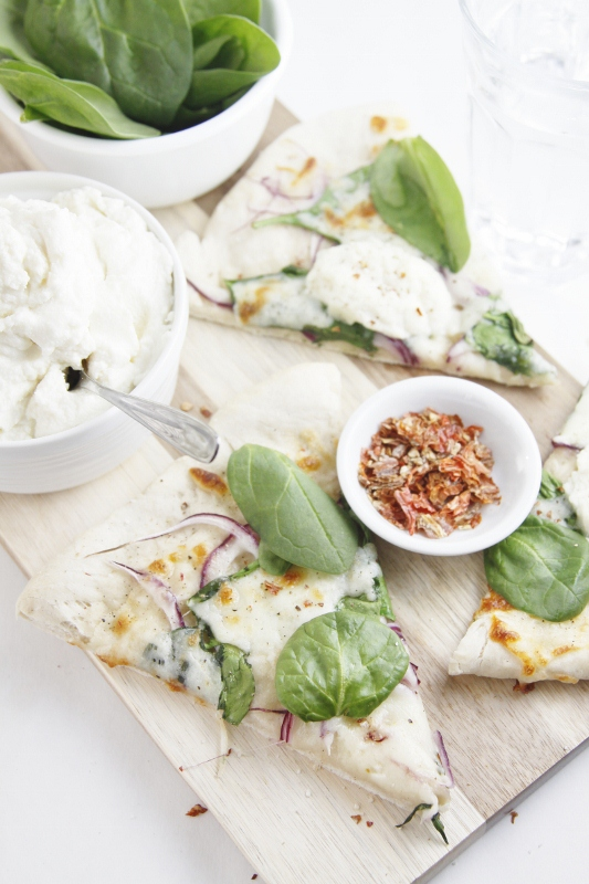 slices of spinach ricotta pizza on cutting board with small bowls of spinach, ricotta and red pepper flakes.