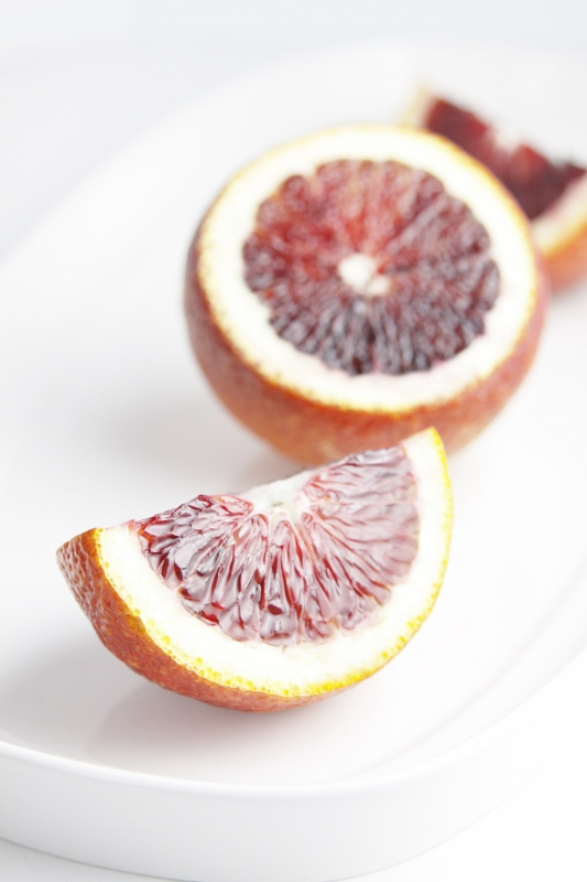 Blood oranges slices on white tray.