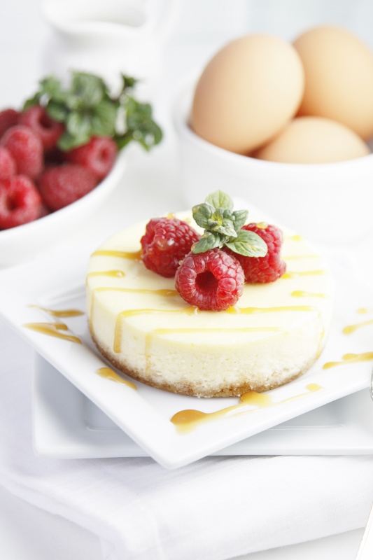 Mini cheesecake on white plate. Garnished with mint, raspberries and caramel sauce. White bowl of raspberries , white bowl of eggs in background.