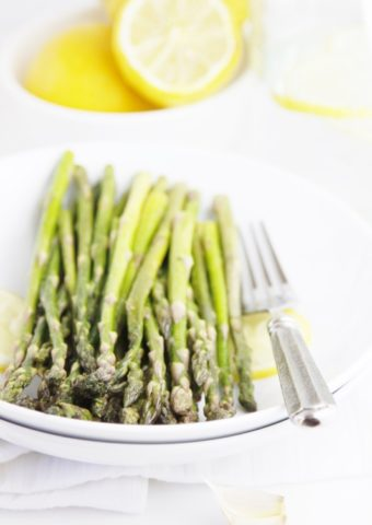 Sauteed Asparagus with Lemon on white plate with fork to side.