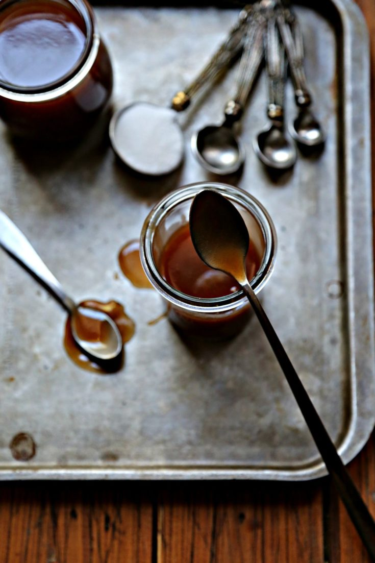 small jars of caramel sauce on baking sheet with spoons