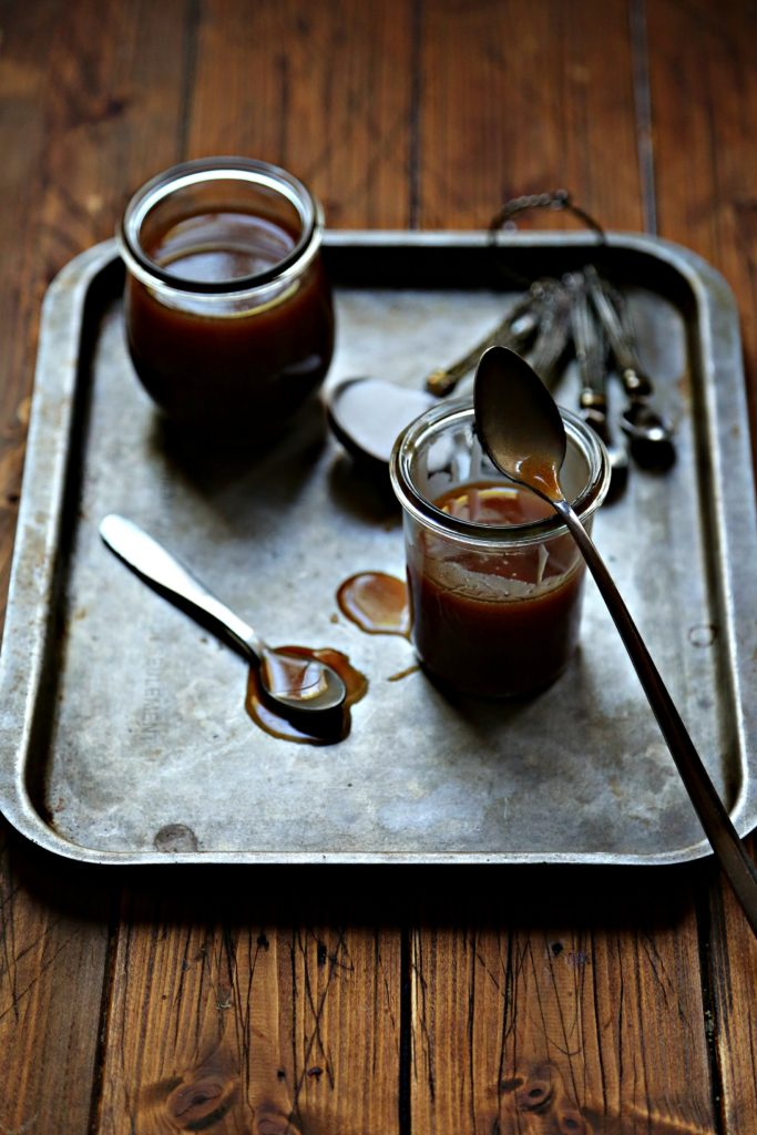 small glass jars of caramel sauce on a baking tray with spoons.