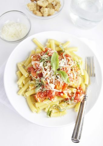 Pasta on white plate with fork to right.