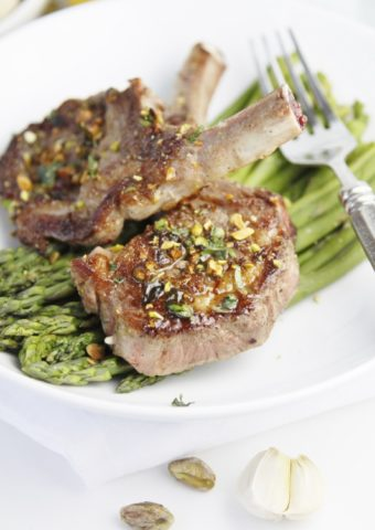 2 lamb chops sitting on top of a bed of asparagus with fork to side.