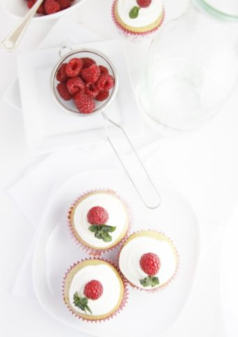 3 cupcakes topped with raspberries on white plate. Small galss bowl of raspberries in background.