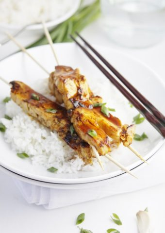 chicken yakitori skewers on a bed of rice in a white bowl. Chopsticks to side.