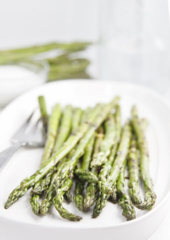 grilled asparagus on white plate with serving fork. Asparagus and glass carafe in background.