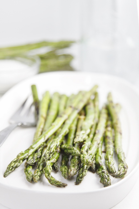 Grilled asparagus on white plate with serving fork to left. Blurred asparagus in background.