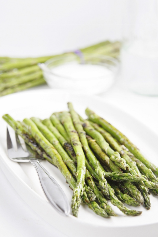 Grilled Asparagus on white plate with serving fork. Asparagus small glass bowl of sugar and glass carafe blurred in background.