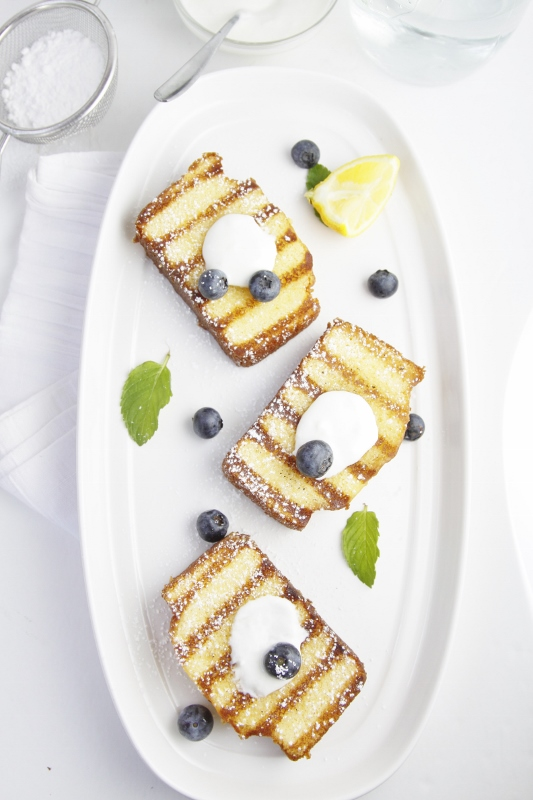 3 slices of grilled pound cake on white tray topped with yogurt and blueberries.