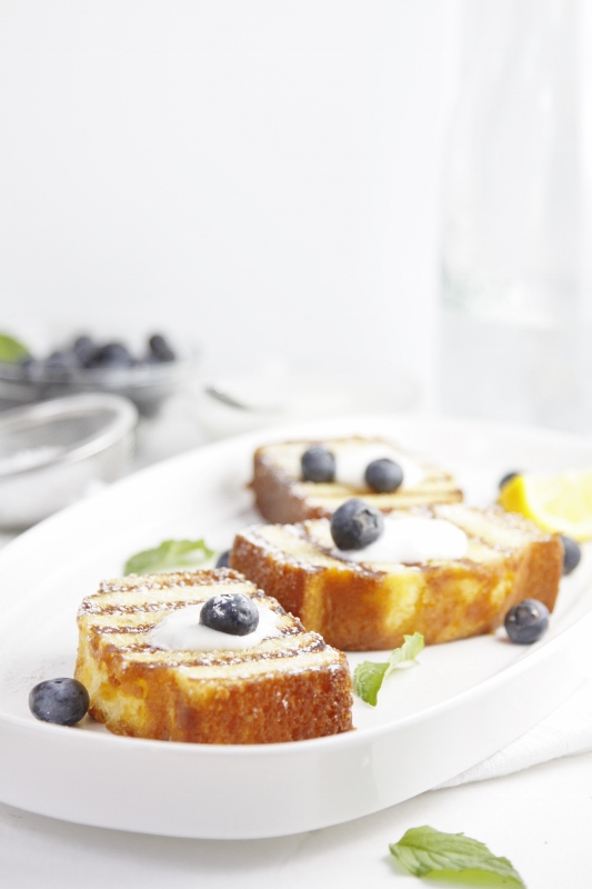 3 slices of Grilled Pound Cake with Blueberries on white tray. Berries and glass carafe in background.