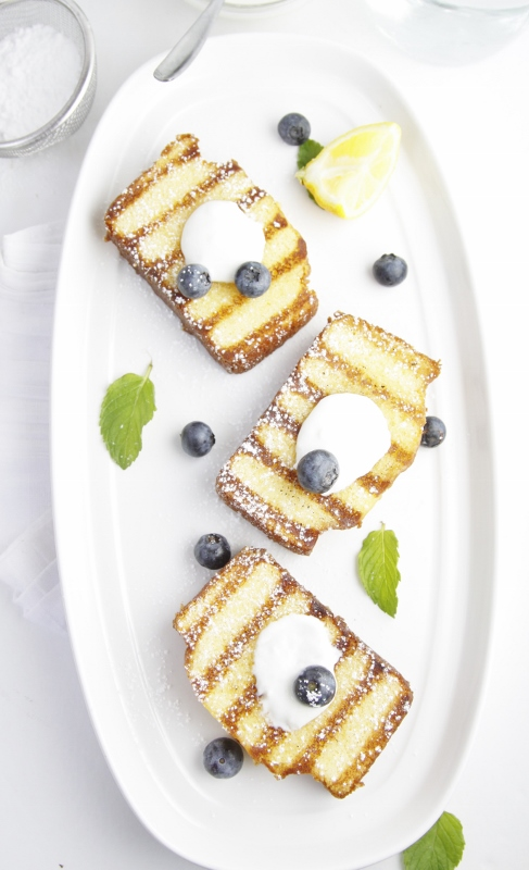 3 slices of Grilled Pound Cake with Blueberries on white tray. Lemon wedges and blueberries scattered around slices.