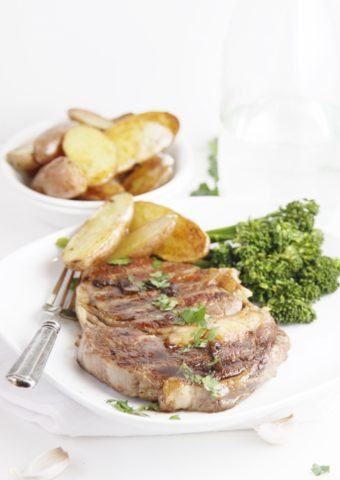 steak with potatoes and broccoli on white plate. White bowl of potatoes in background.