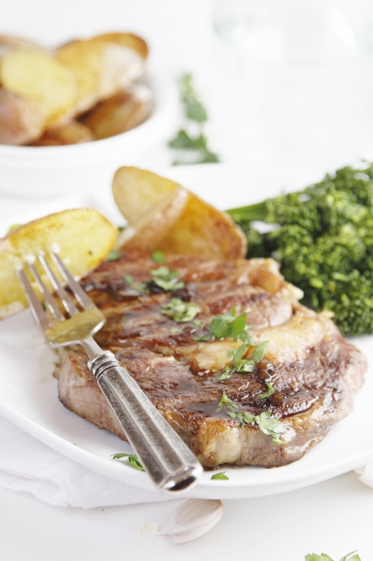 Steak with potatoes and broccoli on white plate. Bowl of potatoes in background.