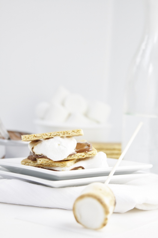 Milk Chocolate Cream Cheese S'Mores stacked on white plate. Marshmallow on skewer to side. Graham crackers, white bowl of marshmallows and a glass carafe are in background.