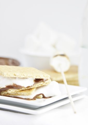 Chocolate Cream Cheese S'Mores stacked on white plate. Skewer with marshmallow to side.