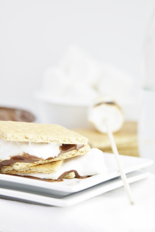 Milk Chocolate Cream Cheese S'Mores stacked on white plate. Marshmallow with skewer sitting on a stack of graham crackers to right. White bowl of marshmallows in background.