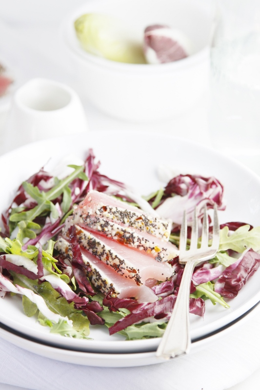 Sesame Seared Ahi Tuna Salad in white bowl. Fork to right. Small white pitcher of dressing, white bowl with endive and glass carafe in background.
