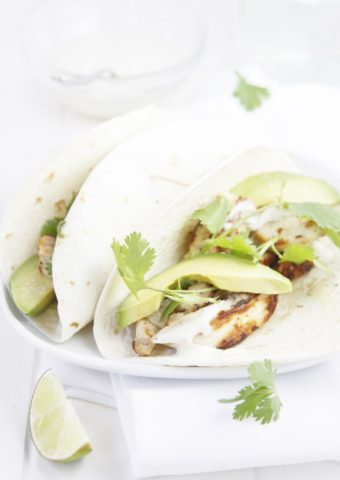 2 chicken tacos on white plate drizzled with jalapeno ranch sauce.