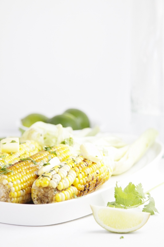 Grilled Corn with Tequila Lime Butter on white tray. Limes in background.
