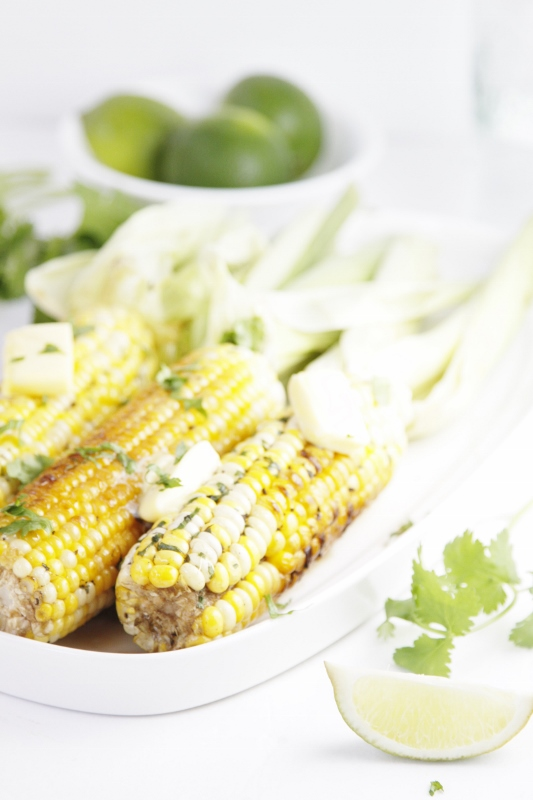 Grilled Corn with Tequila Lime Butter on white tray. Small bowl of lime in background with sprigs of cilantro to side.