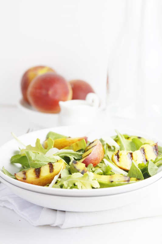 Grilled Peach and Avocado Summer Salad in white bowl. Peaches and glass carafe in background.