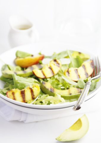 Grilled Peach and Avocado Summer Salad in white bowl with fork. Small white pitcher of salad dressing in background.