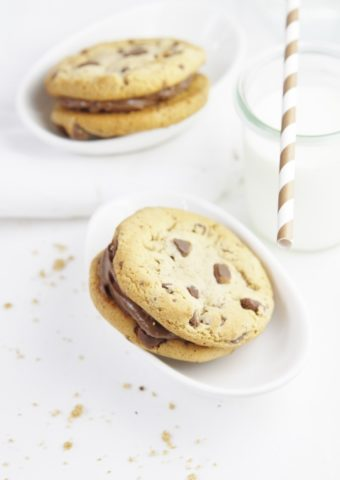 cookie sandwiches in white bowls. Striped straw with glass of milk to side.