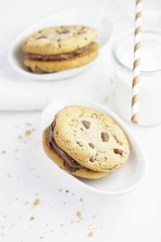Milk Chocolate Cookie Sandwiches in white bowl. Glass of milk with striped straw to side.
