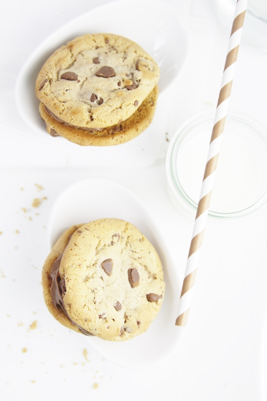 Milk Chocolate Cookie Sandwiches in white bowls. Glass of milk with striped straw to side.