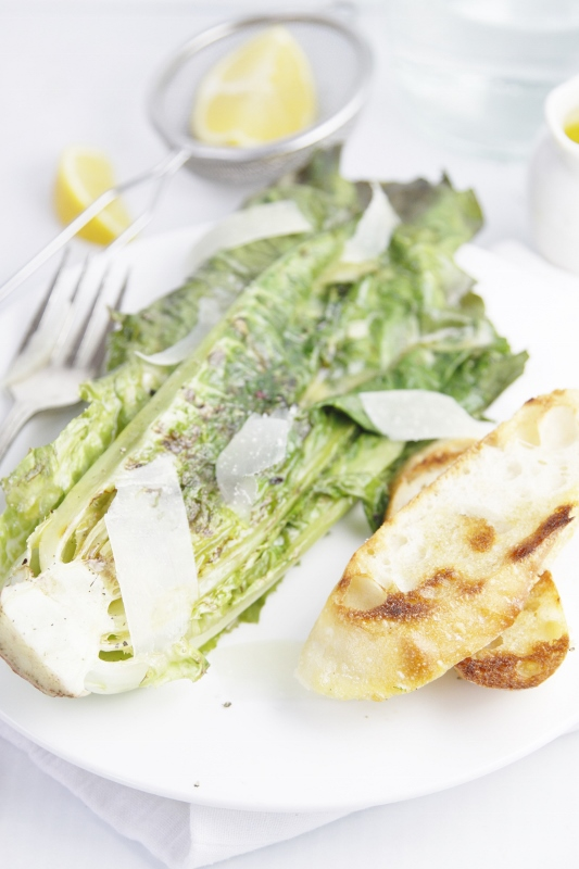 Grilled Caesar Salad on white plate with fork. Lemon wedges in background.