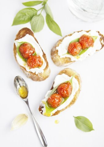 Roasted tomato and ricotta crostini with spoon with olive oil to side.