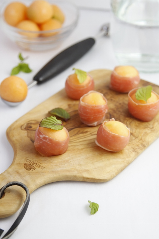 Prosciutto Wrapped Melon Balls on cutting board with melon scoop.
